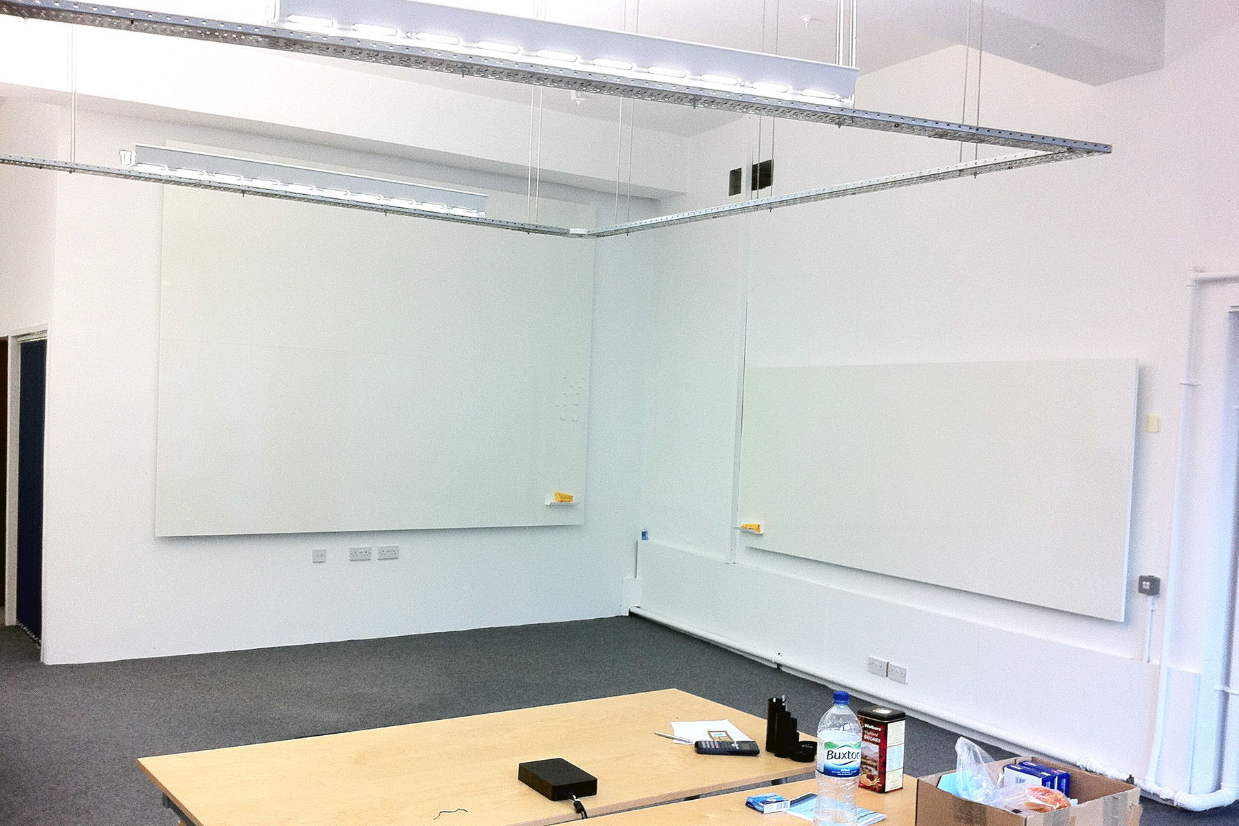 Frameless Whiteboard in two sizes on adjacent walls in the corner of an office